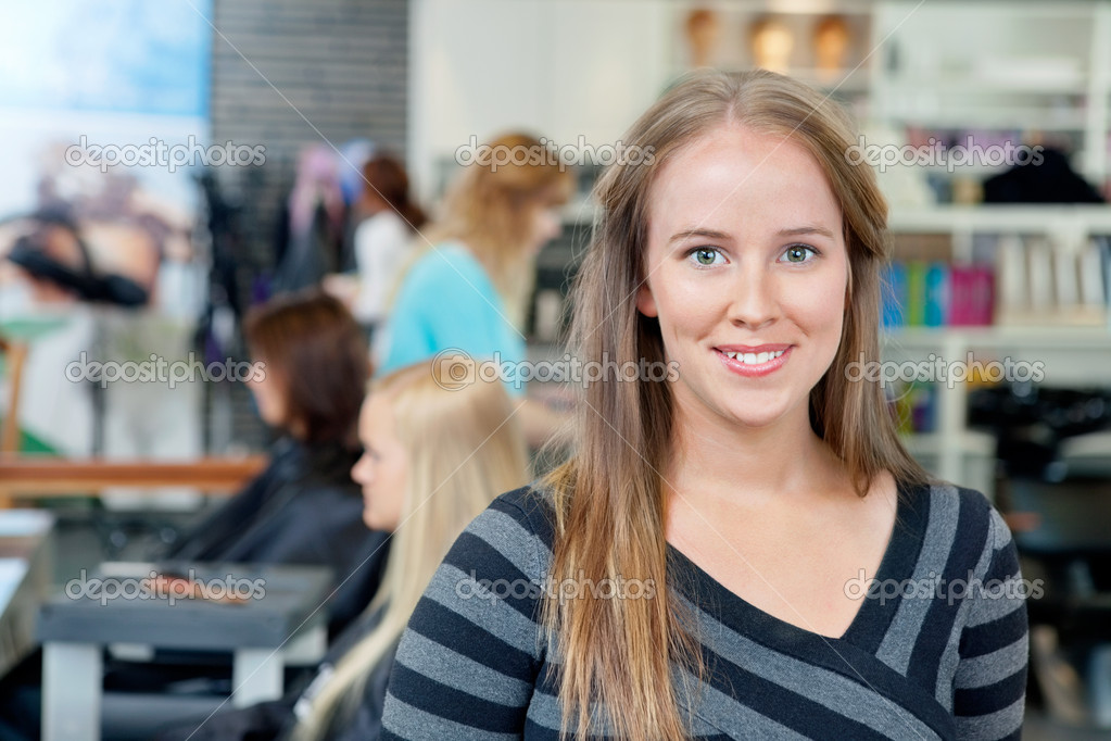 Portrait of young female hairdresser smiling with in background — Stock Photo #11660260