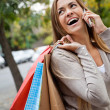 Woman On A Call While Carrying Shopping Bags - Stock Photo