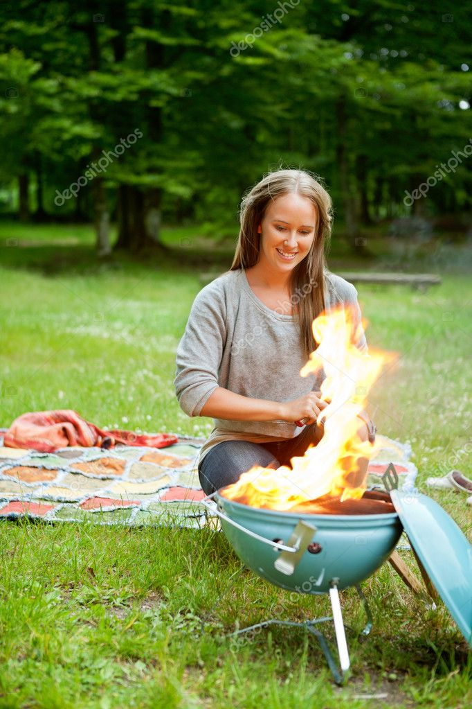 Beautiful young woman sitting in front of flaming portable barbecue at an outdoor picnic — Stock Photo #11794871