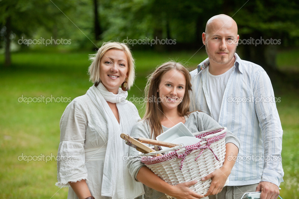 Portrait of a cute young female holding picnic basket while standing with parents — Stock Photo #11795514