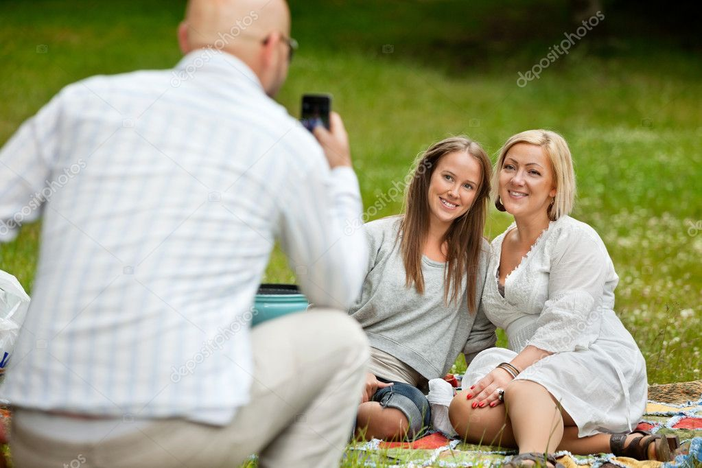 Rear view of man taking picture of friends with cell phone — Stock Photo #11796624