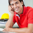Foto Stock: Happy Architect Sitting By Desk