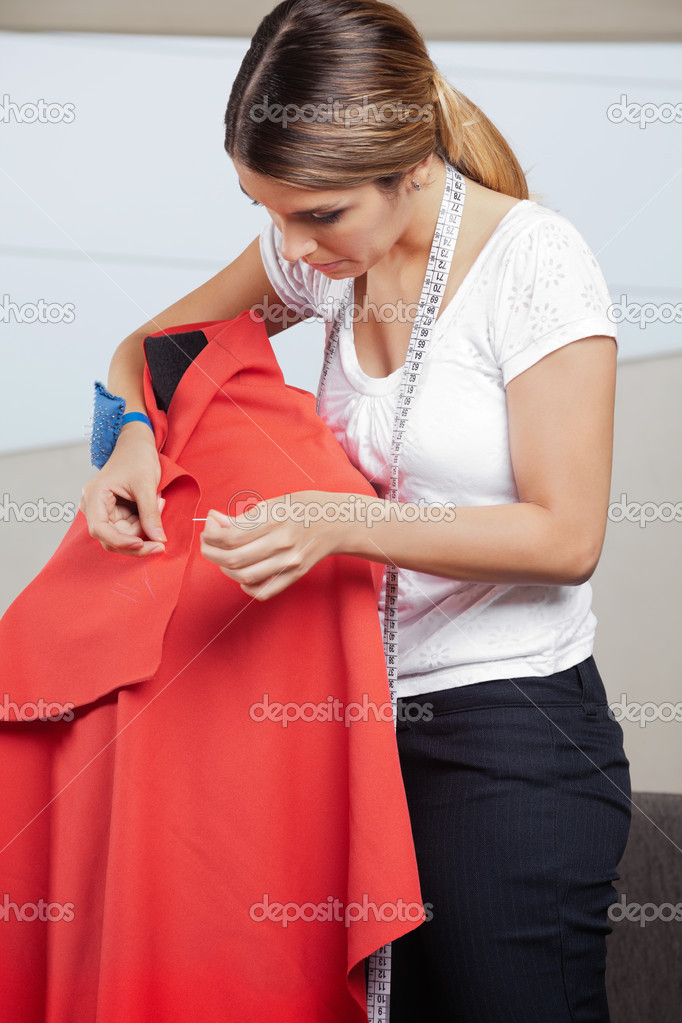 Young female fashion designer adjusting pins on a red fabric draped on mannequin — Stock Photo #12190506