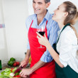 Laughing Couple Cooking in Kitchen - Stock Photo