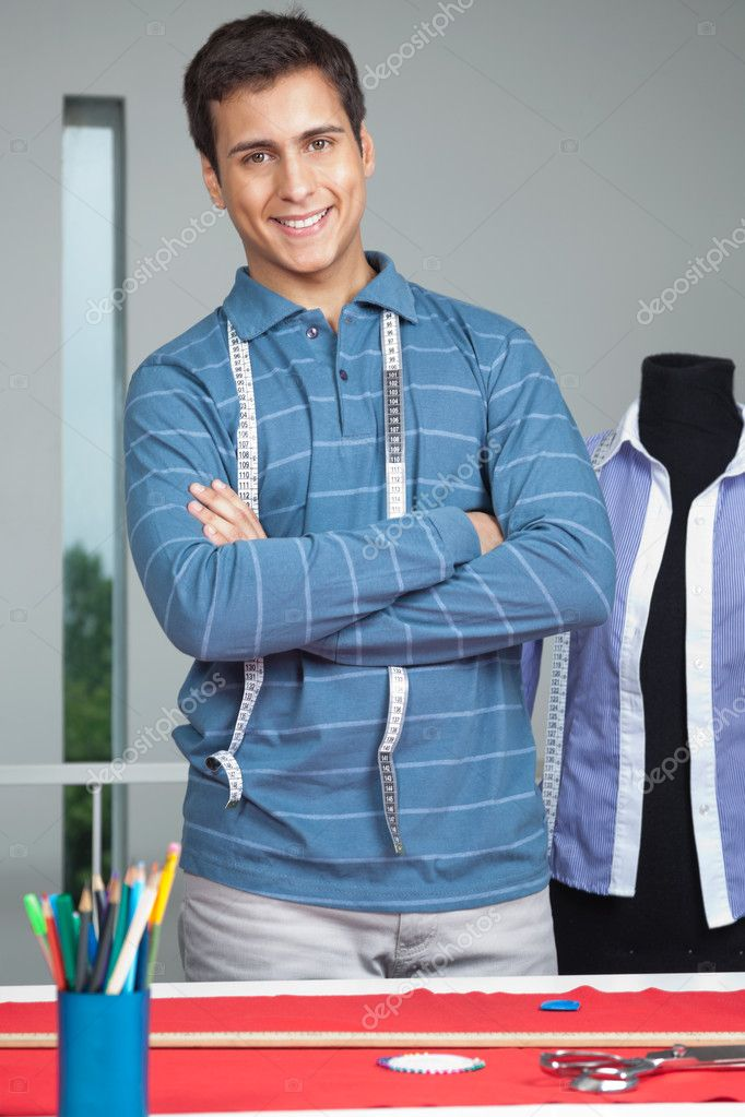 Portrait of young male tailor standing arms crossed by table with mannequin in background — Stock Photo #12219346
