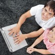 casal no tapete com laptop — Foto Stock