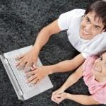 coppia sul tappeto con il portatile — Foto Stock