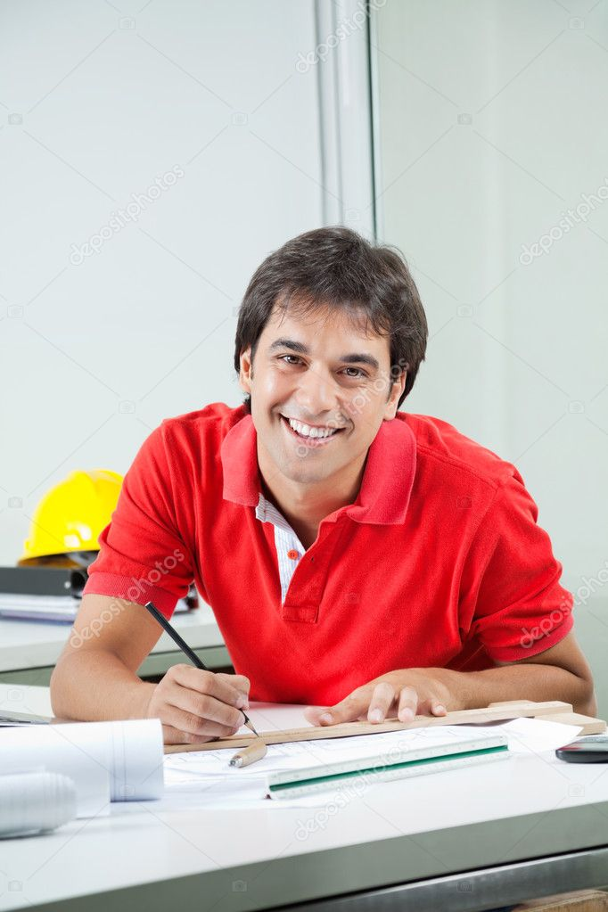 Portrait of young male architect drafting blueprint while sitting at desk — Stock Photo #12223288