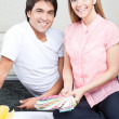 Happy Young Couple with Blueprints and Color Swatches - 