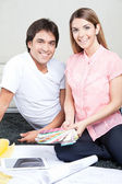 Happy Young Couple with Blueprints and Color Swatches — Stock Photo