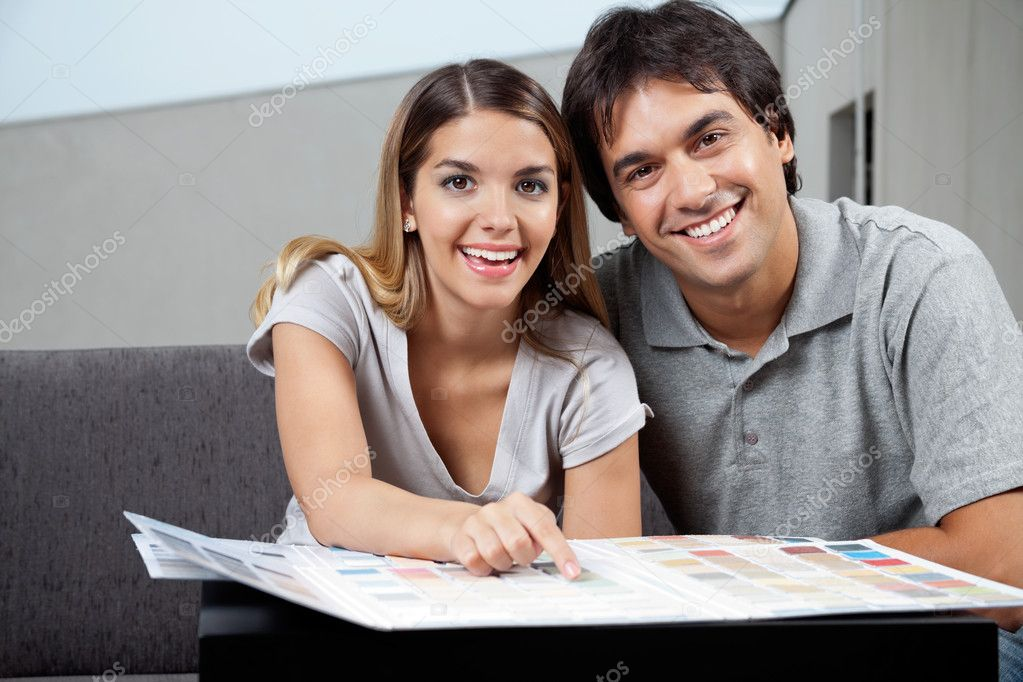 Portrait of happy young couple choosing paint colors from swatch chart — Stock Photo #12259458