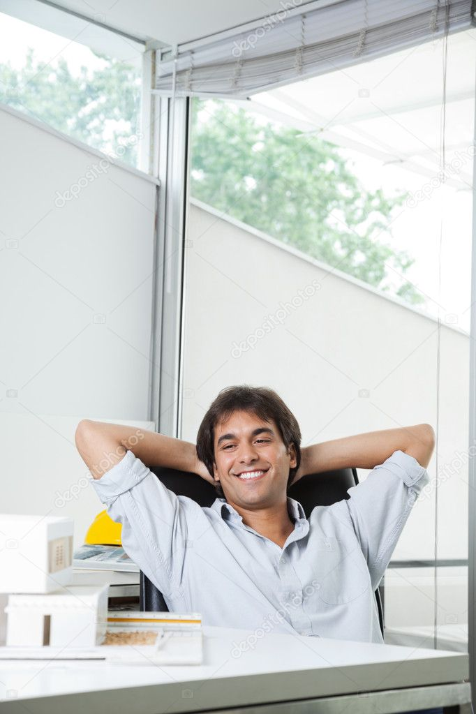 Happy young male architect looking at model house while sitting in chair with hands behind head — Stock Photo #12259823