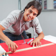 Happy Dressmaker Measuring Red Fabric - Stock Photo