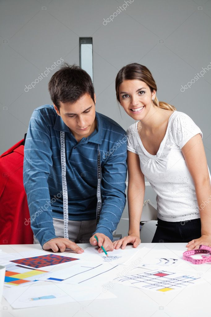 Portrait of young female fashion dressmaker with colleague working on rough outlines designs at workshop — Foto Stock #12260003
