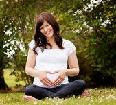 Glada leende gravid kvinna i park — Stockfoto