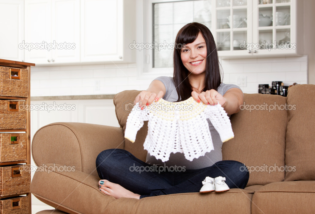 Portrait of expecting mother holding up knitted sweater — Stock Photo #12328525