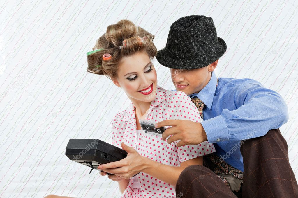 Retro styled young couple holding an old fashioned cassette player over textured background  Stock Photo #12329211