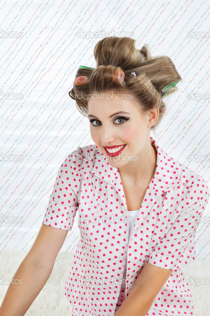 Portrait of an attractive young woman smiling with curlers in hair — Stock Photo #12329226