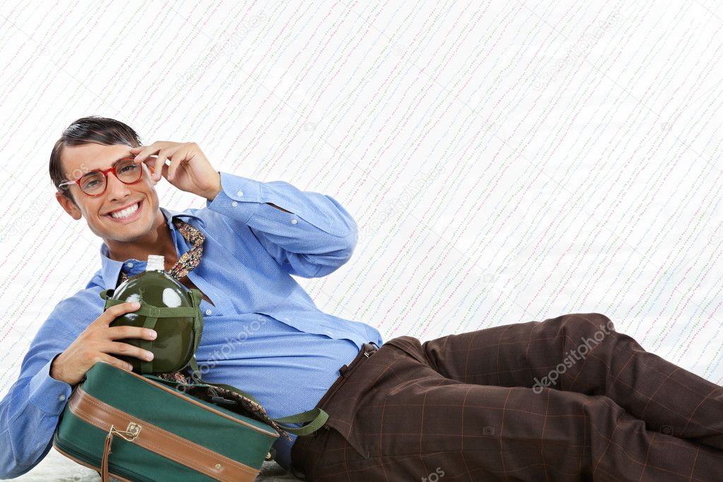 Portrait of happy geek businessman lying down with travel bag on textured background — Stock Photo #12329330
