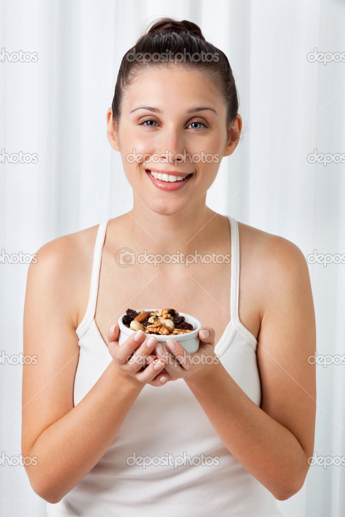Portrait of an attractive young woman holding bowl of dry fruits  Stock Photo #12330549