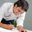 Stock Photo: Architect Working On Blueprint
