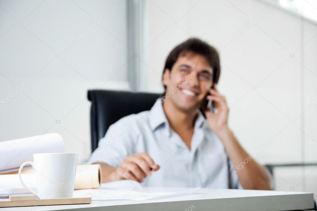 Focus on coffee cup with male architect answering phone call in background — Stok fotoğraf #12379094