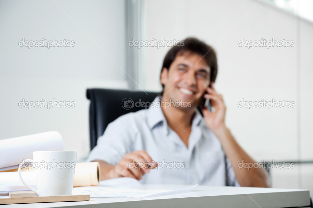 Focus on coffee cup with male architect answering phone call in background — Zdjęcie stockowe #12379094