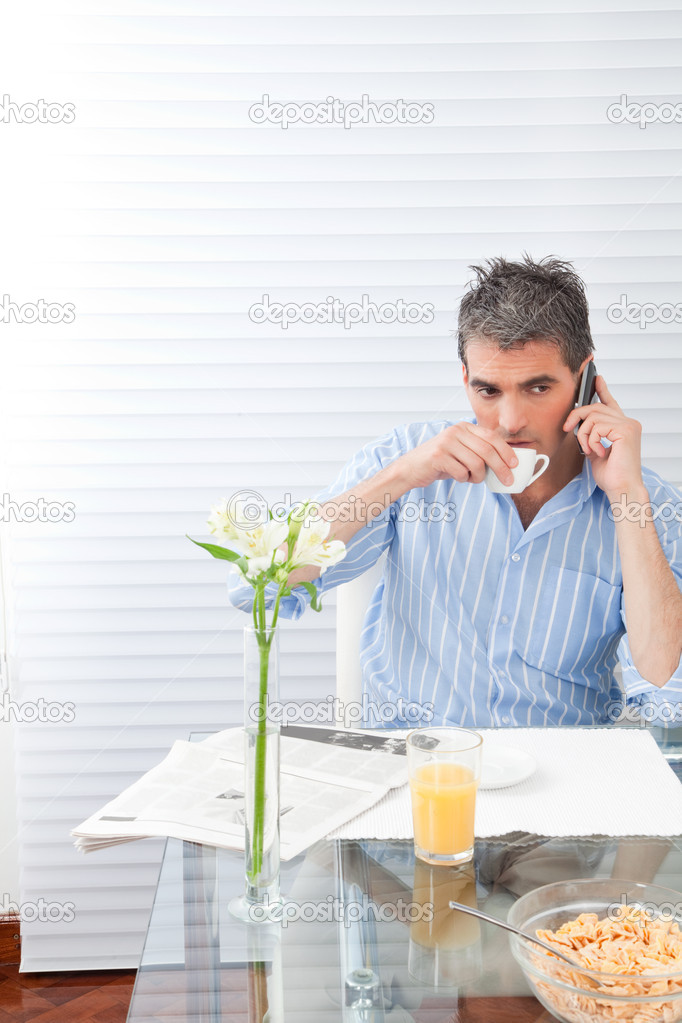 Mature man having breakfast using phone. — Stock Photo #12381951