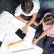 Couple Sitting On Rug With House Plans — Stock Photo #12395328