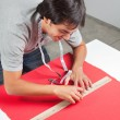 Dressmaker Measuring Red Fabric - Stock Photo