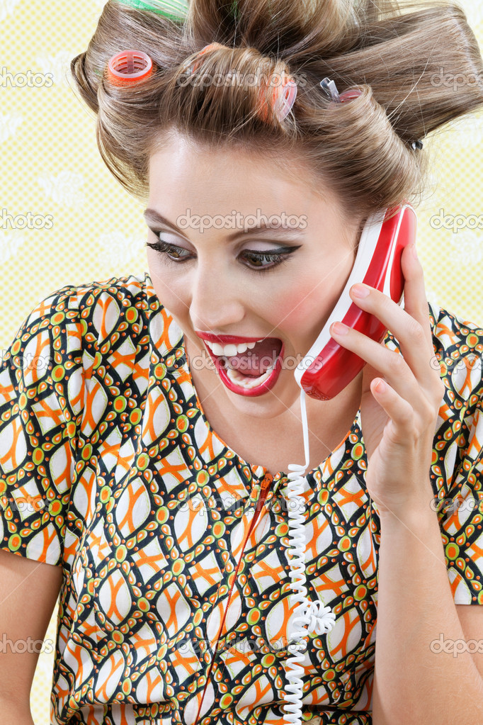 Young woman with hair curlers screaming out while holding a telephone — Stock Photo #12394968