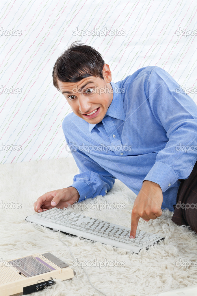 Geek businessman lying on rug with computer keyboard and vintage cassette player  Stock Photo #12395022