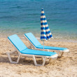 Two blue lounge chairs on a beach in Hanioti - Stock Photo