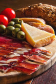 Platter of antipasti appetizers, with crusty bread — Stock Photo