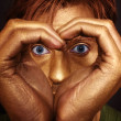 Man's face with her hands folded in the shape of a heart - Stock Photo