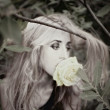 Stock Photo: Beautiful young woman with white rose in his mouth