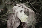 Beautiful young woman with white rose in his mouth — Stock Photo
