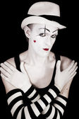 Studio portrait of mime in white hat and striped gloves — Stock Photo