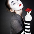 Dreaming woman mime with red flower — Stockfoto
