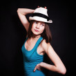 Stock Photo: Young woman in white hat on black background