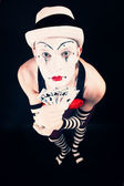 Circus clown in makeup with playing cards on a black background — Stock Photo