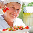 The elderly woman shows a crop - strawberry — Stock Photo