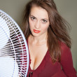Stock Photo: The fan blows to face of woman
