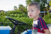The boy drives a small tractor — Stock Photo