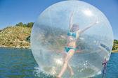 Joyful girl in a balloon floating on water. — Stock Photo