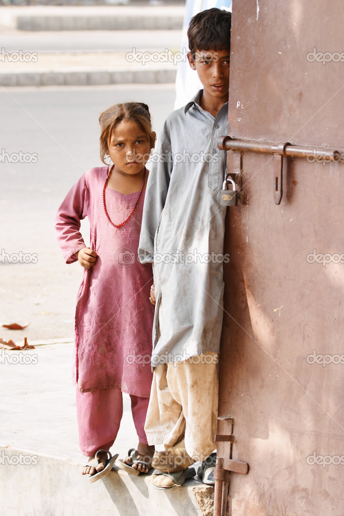 Two needy pakistani children standing at the door of the shop and waiting for charity, Karachi, Pakistan — Stock Photo #11517092