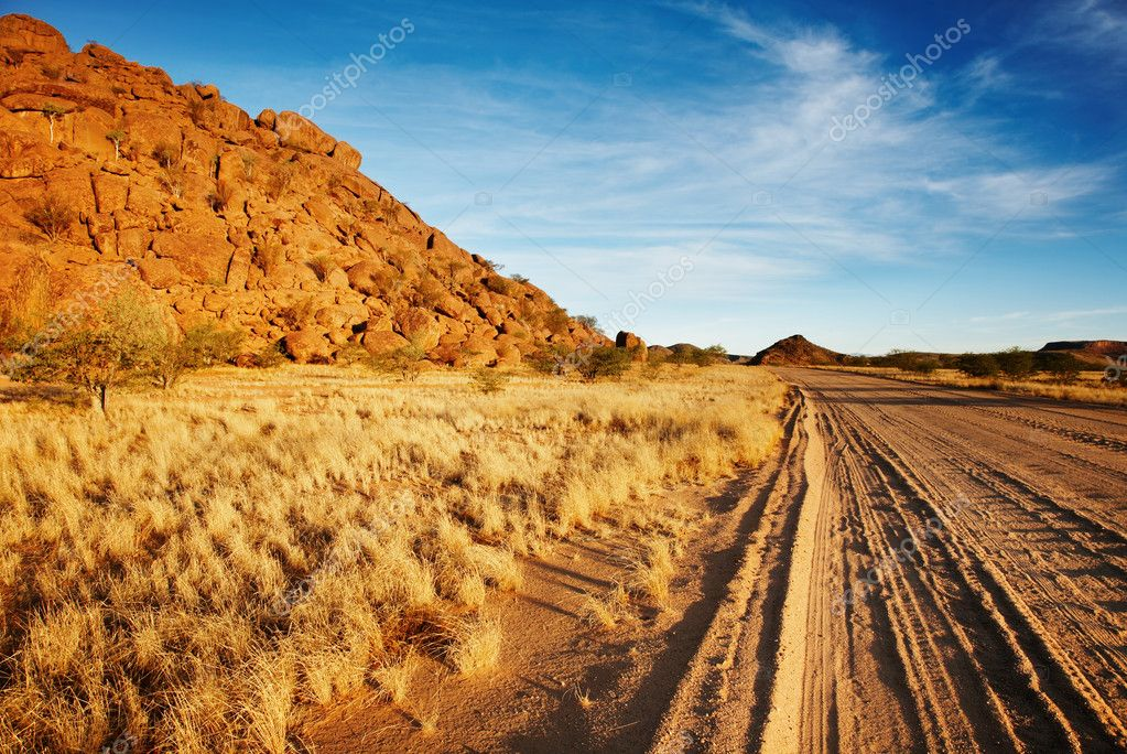 Desert landscape with dusty road and blue sky  Stock Photo #11520106