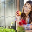 Portrait of girl with red apple against green garden. — Stockfoto