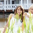 Two youngl pretty women in a park one of them points at somethin — Stock Photo