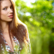 Beautiful young brunette woman standing near garden — Stock Photo